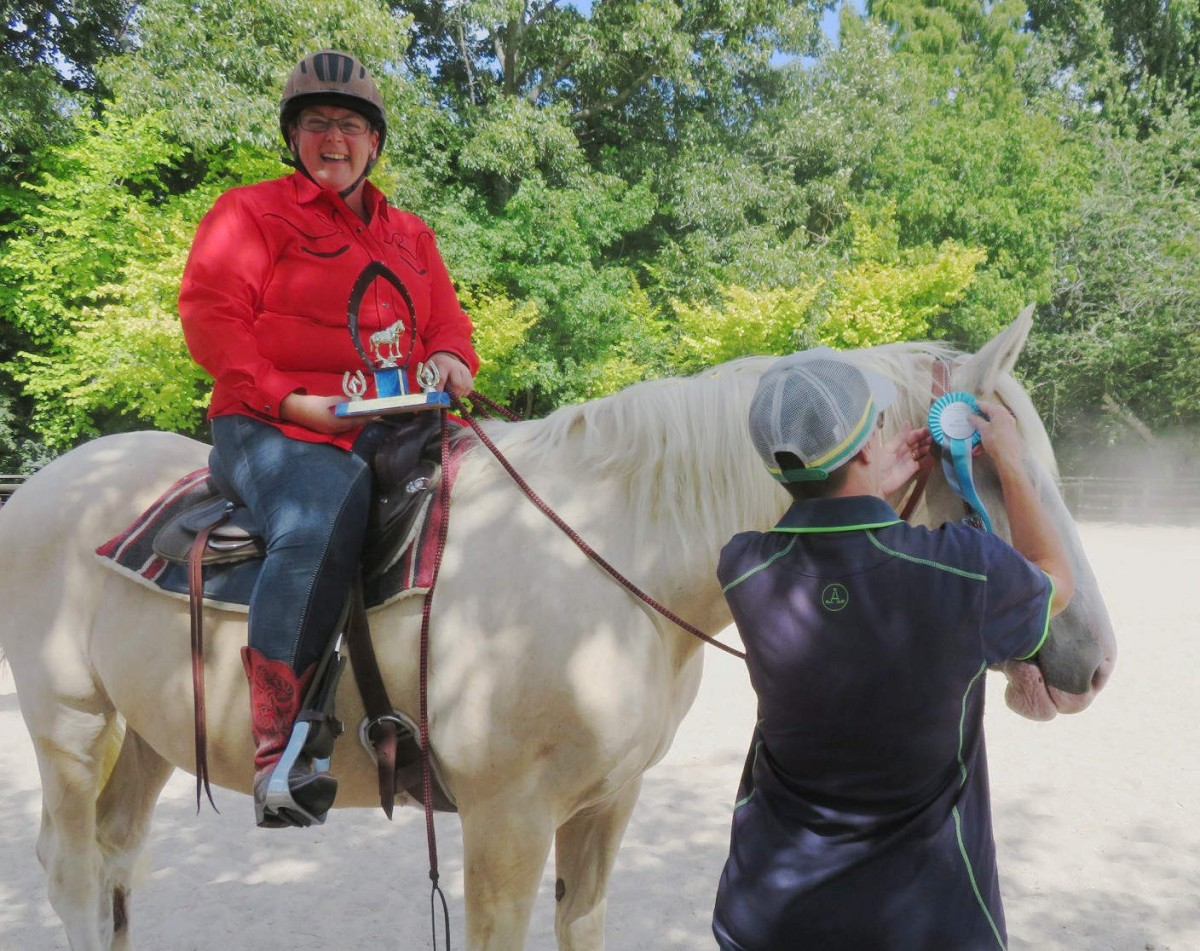 Karen awarding a rosette to a rider and horse